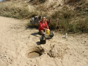 Bev washing laundry in dry riverbed.